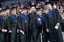 Several men in caps and gowns pose for a photo during MCC graduation ceremony
