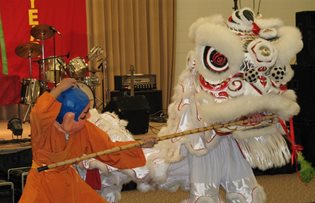 Two costumed people engaged in dragon and stick dance for Vietnamese New Year
