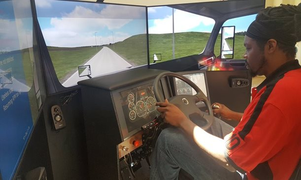 A man concentrates in a truck-driving simulator